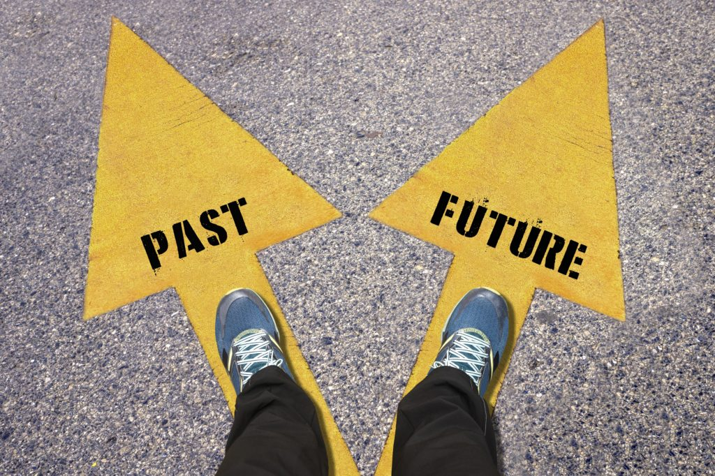 Feet and words Past and Future , Choice Concept - business man walking with arrow on the road , Two Yellow Arrows Painted on Asphalt showing different directions