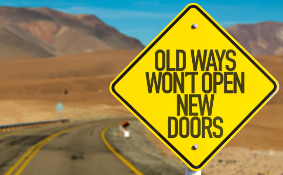 Old Ways Won't Open New Doors written on a yellow road sign