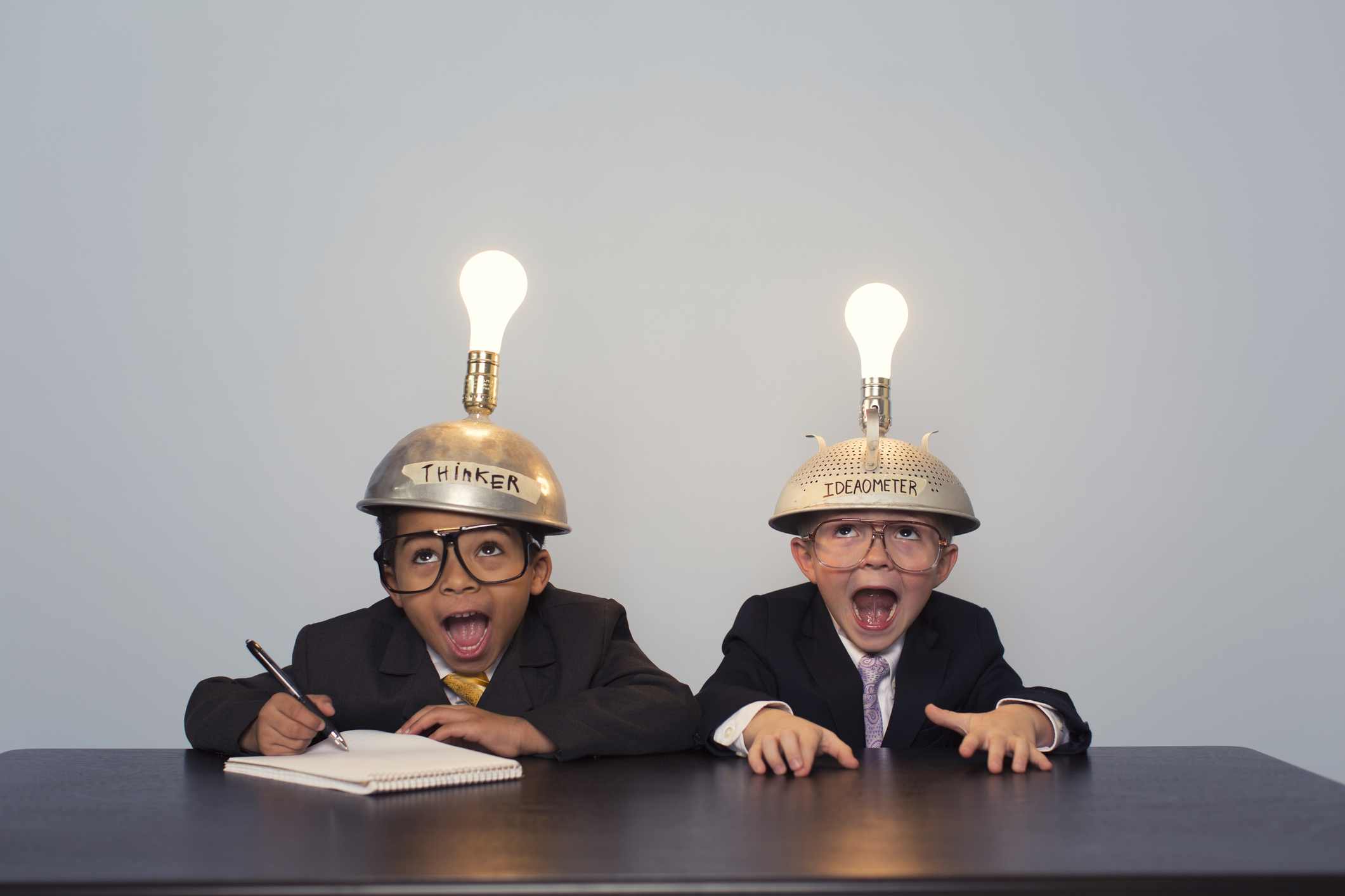Two boys thinking in suits wearing thinking caps