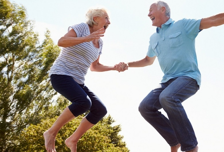 An older couple jumping in the air
