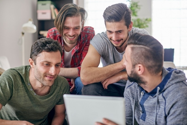 Group of four male friends gathered round a laptop
