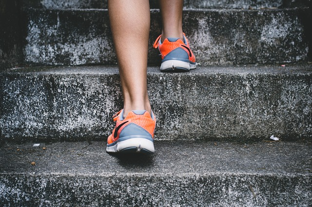 close up of a person wearing ttrainers walking up stone steps