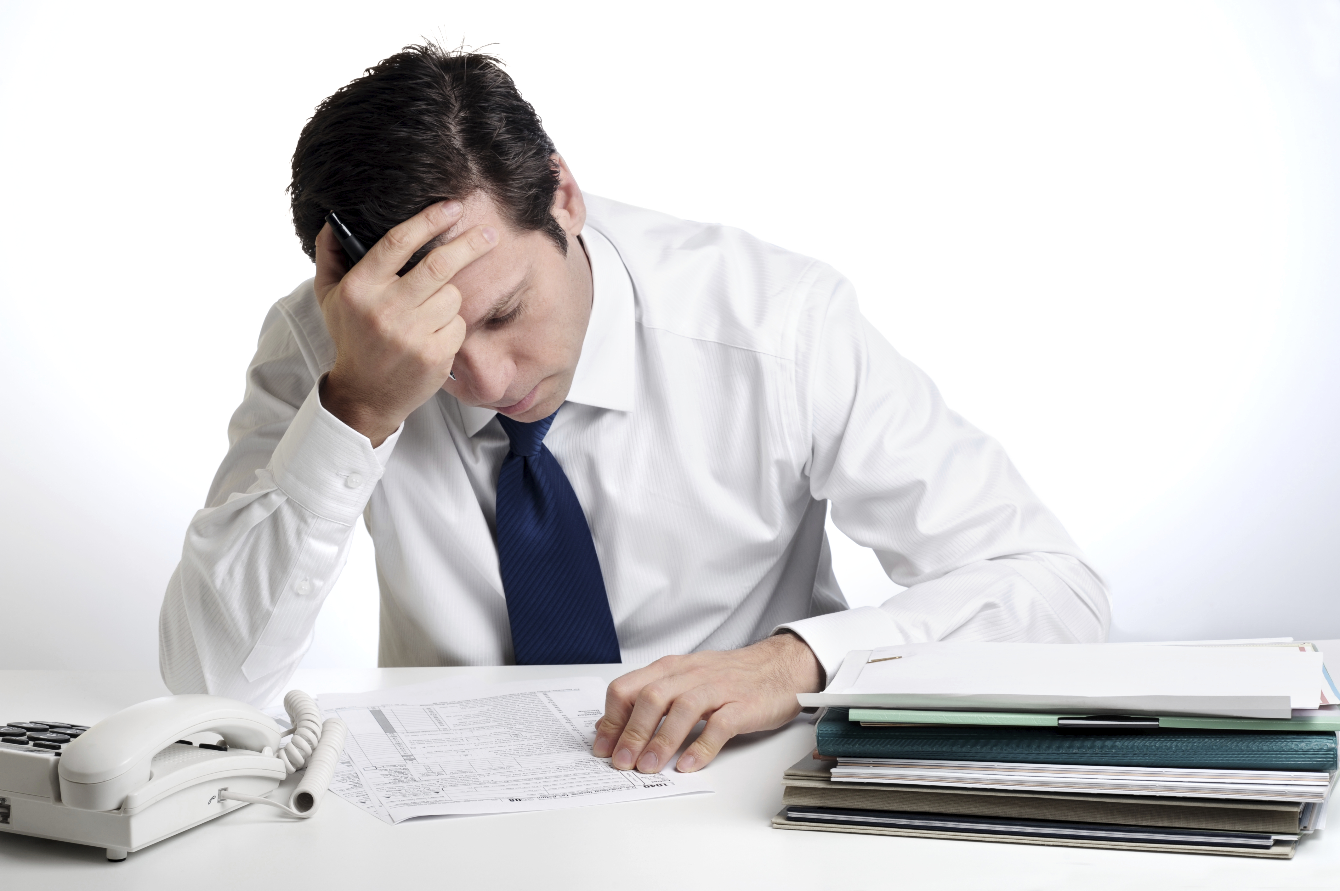 Business Man Sitting at a Desk Struggling to Complete Paperwork