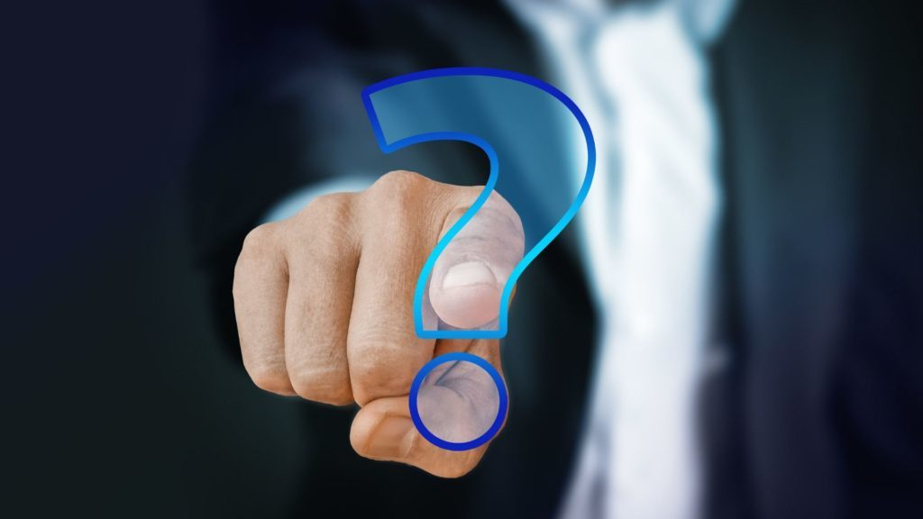 Man in a suit pointing to a question mark that has a blue outline