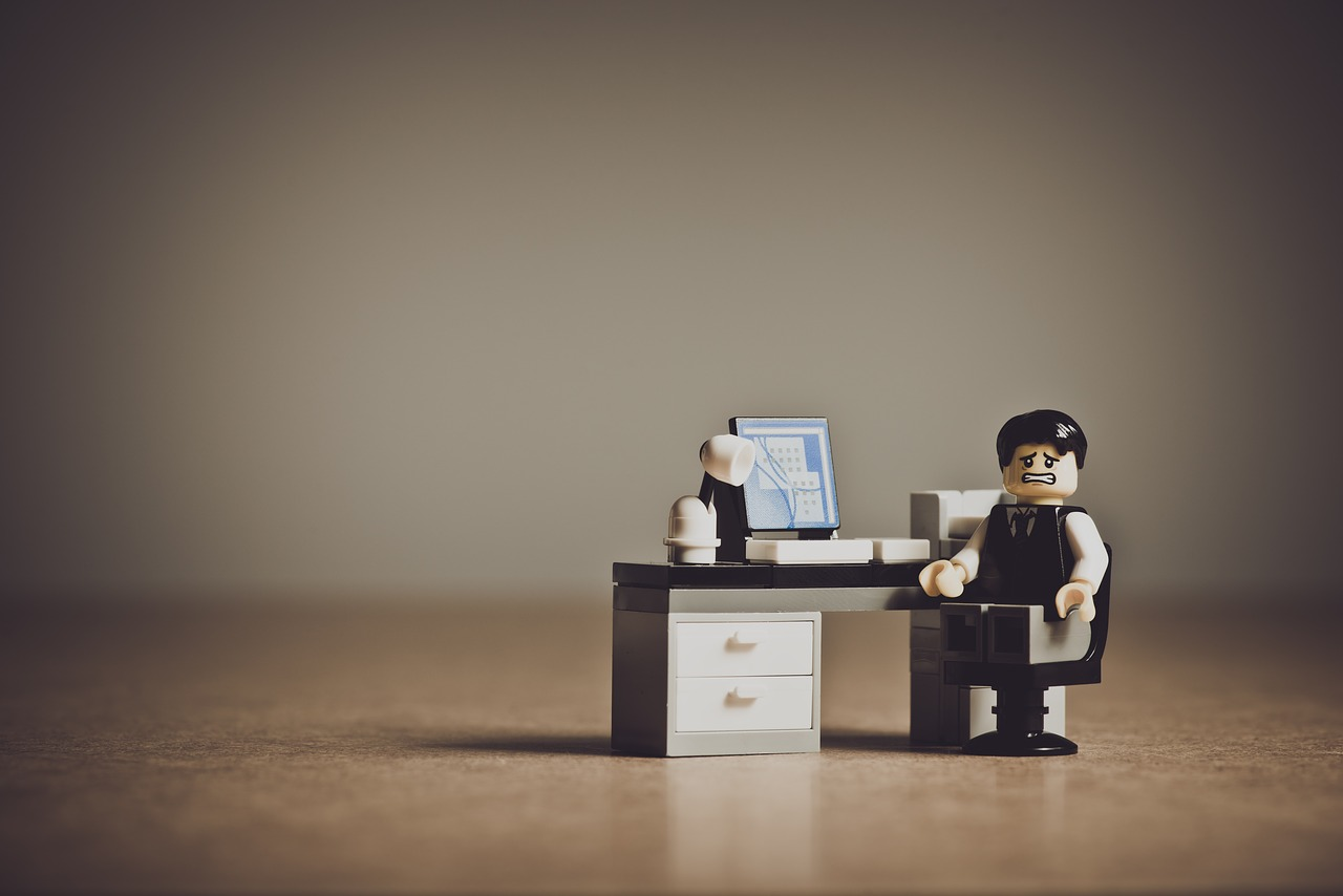 Lego man sitting at his lego desk looking worried