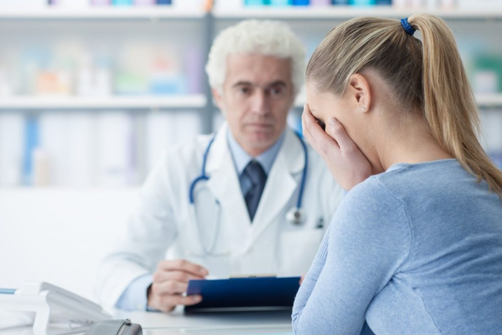 Doctor and Patient sitting talking about diagnosis'. The patient has her head in her hands