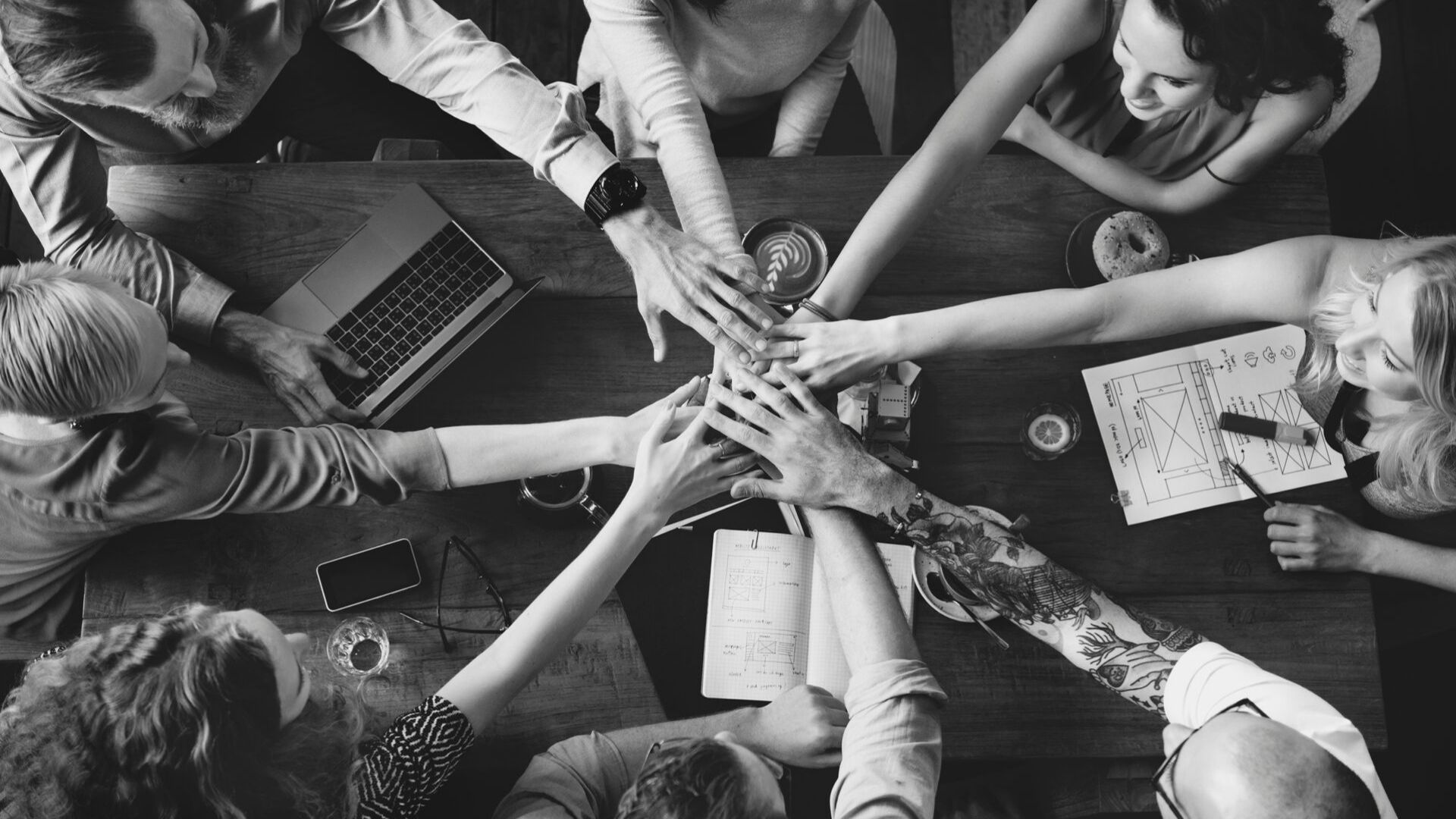 corporate team all putting their hands in the centre as a sign off unity