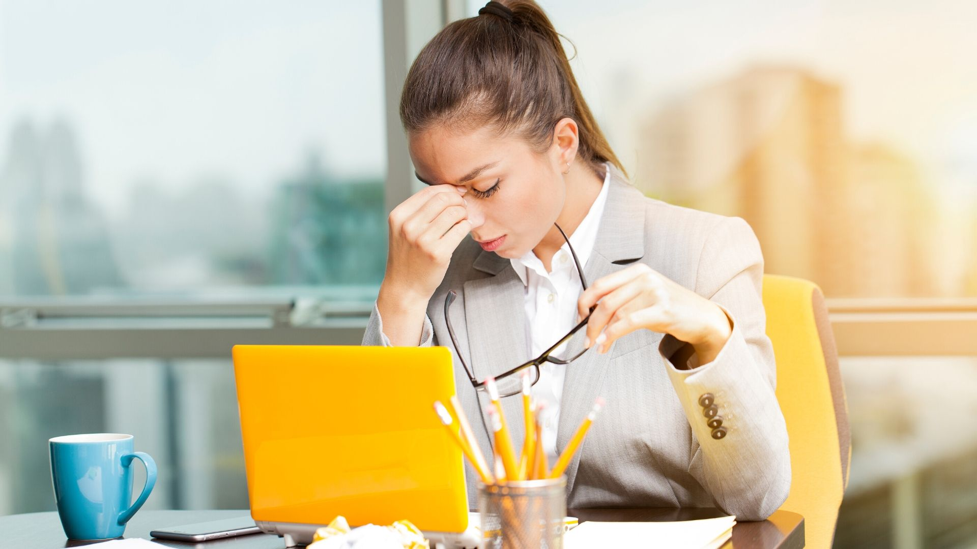 woman sat at her office desk looking stressed