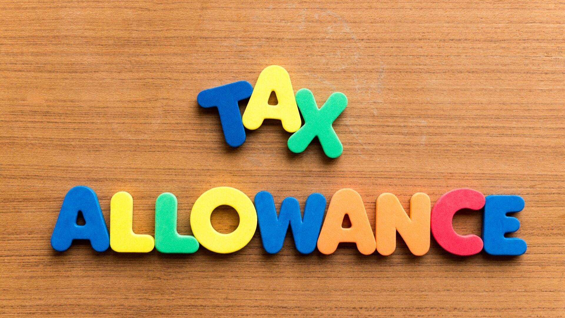the words tax allowance are spelled out using plastic letters on a brown desk