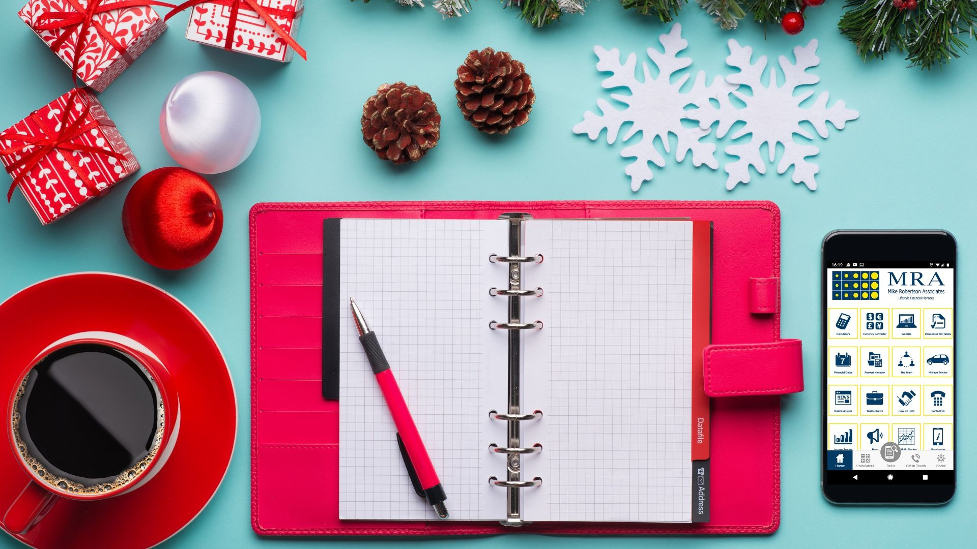 red filofax open on a turquoise desk with paper snowflakes and pine cones scattered around