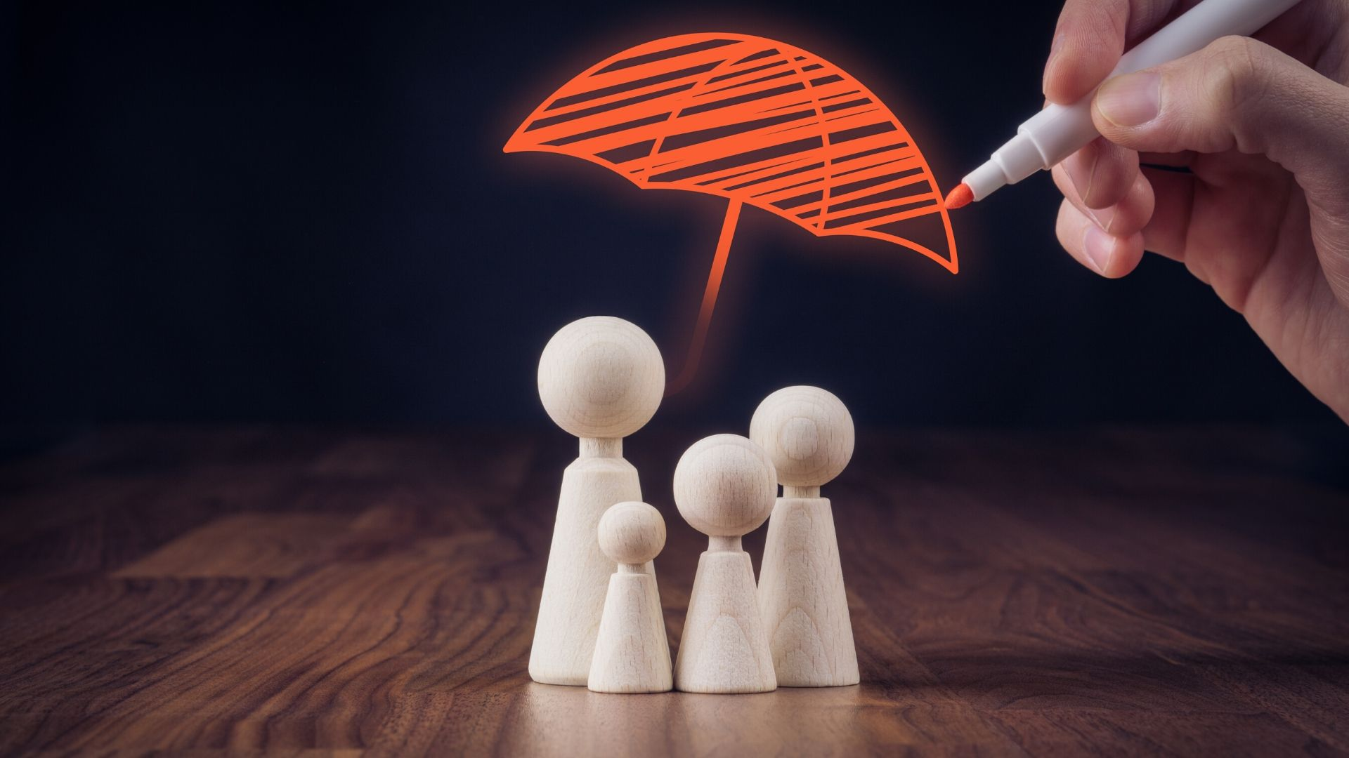 image of 4 wooden figures representing a family with someone drawing an umbrella over the top of them with an orange pen, representing financial protection