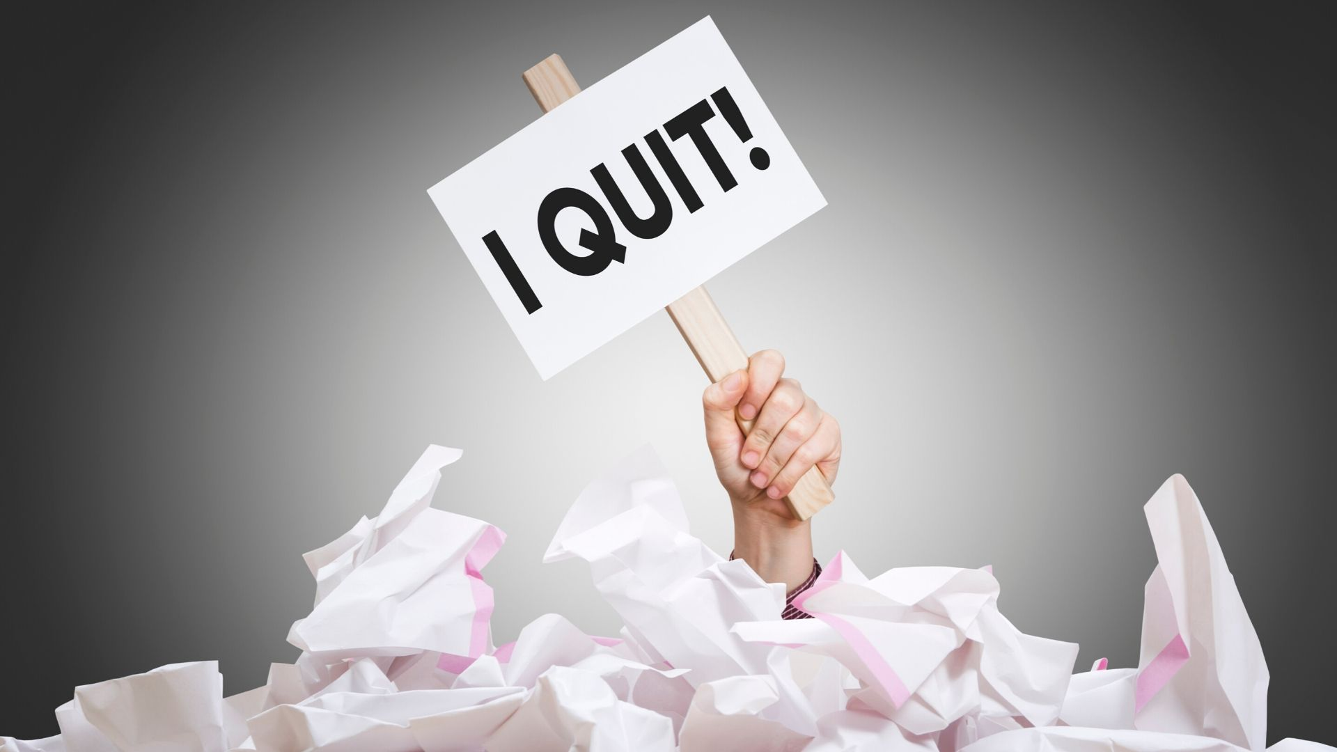 p[lies of srewed up paper with a hand poking out of the top holding a sign that says 'I Quit'