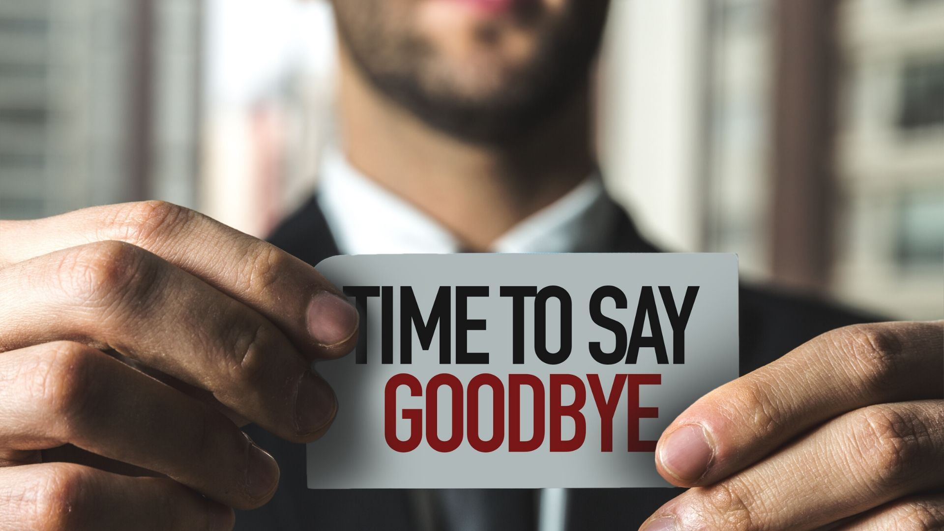 close up of man holding a sign that says 'time to say goodbye'
